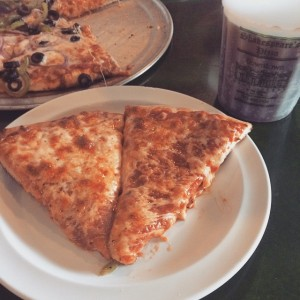 Two slices of Shakespeare's pizza next to their iconic cup